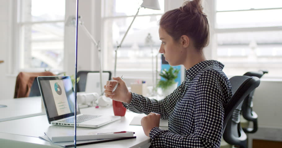 Young business woman working at shared desk in trendy hipster start up office using big data on laptop computer #13948937