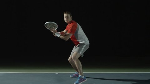 A man playing tennis front shot, on a court at night, hitting balls over the camera's perspective