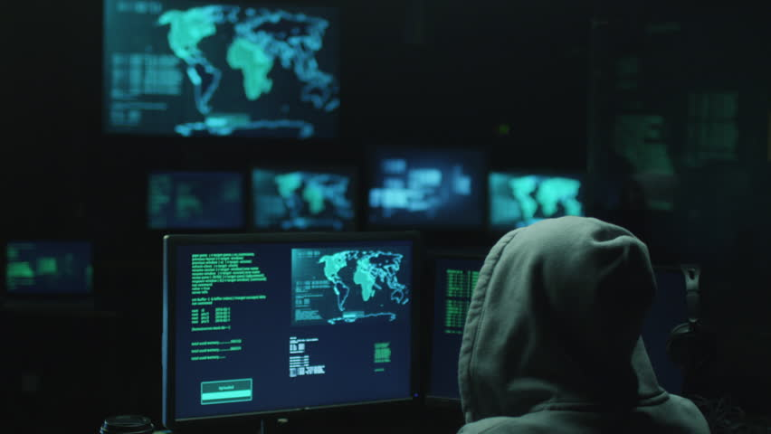 Male hacker in a hood works on a computer with maps and data on display screens in a dark office room. Shot on RED Cinema Camera in 4K (UHD).