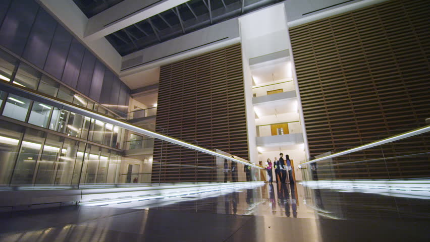 contemporary office building. 4k / Ultra HD Version Attractive Diverse Business Group Walking Through One Of The Floors Contemporary Office Building