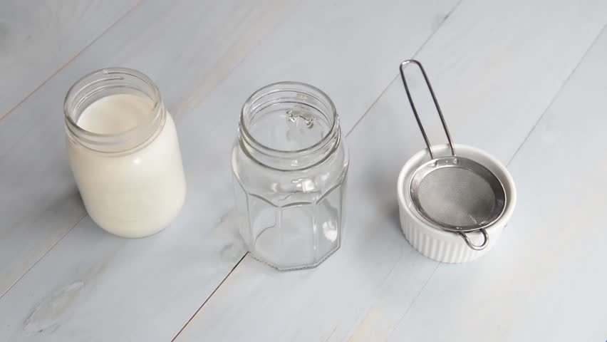 Making Kefir: Close up of hands filtering kefir grains from kefir and pouring into glass jar | Shutterstock HD Video #14034527