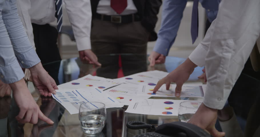 4k / Ultra HD version A diverse group of professionals are brainstorming in a business meeting in a room with lots of computer screens. They are seated around a glass table. In slow motion. | Shutterstock HD Video #14050418