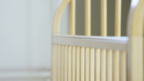 Pregnant woman looking over crib