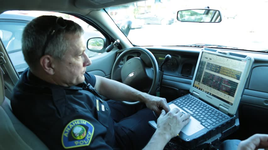 Anaheim, CA., January 2016: Policeman typing on a his laptop in his patrol car