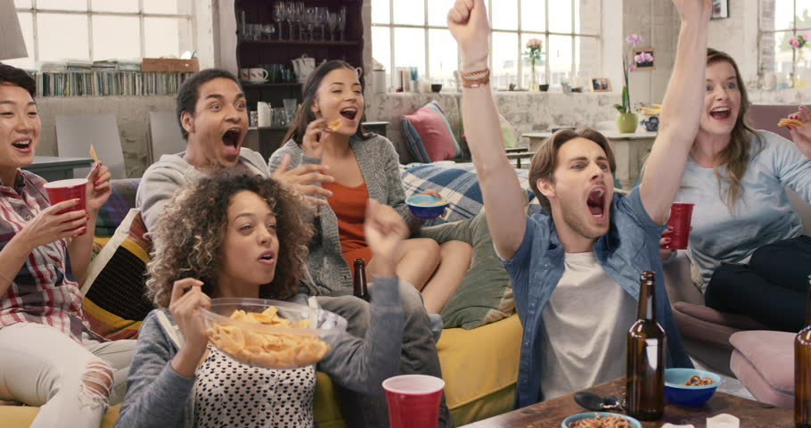 Happy diverse group of student sports fans throwing arms up in excitement celebrating goal watching sports event on TV together bonding as friends eating snacks drinking beer