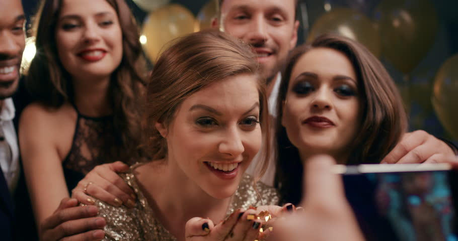 Friend taking video of Beautiful woman blowing glitter at glamorous party having fun with sexy fashion friends for social media