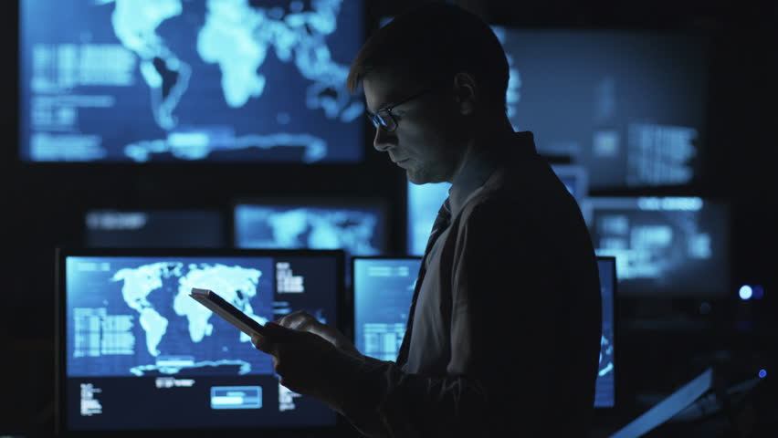 Man in glasses is using a tablet computer in a dark monitoring room filled with display screens. Shot on RED Cinema Camera in 4K (UHD).   Shutterstock HD Video #14097557