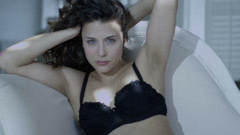 4k / Ultra HD version Beautiful brunette model in black lingerie reclines on a chaise and relaxes in the sunlight from the window. Shot on RED Epic