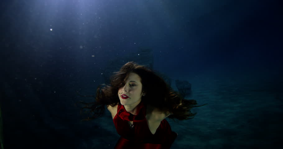 4k / Ultra HD version Beautiful mysterious woman underwater with flowing brunette hair and a red satin dress. Shot on RED Epic