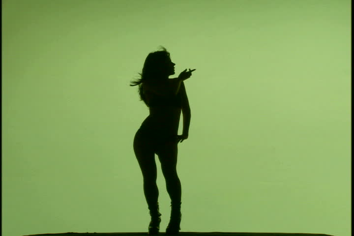 A woman's silhouette dancing against green background