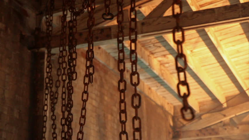 Multiple rusty chains hanging from warehouse ceiling | Shutterstock HD Video #1412221