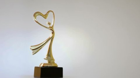 Prize statuette rotates on its axis. Long shot. Loop Gold statue rotates on its axis. Looped video for web development. Internet site design.