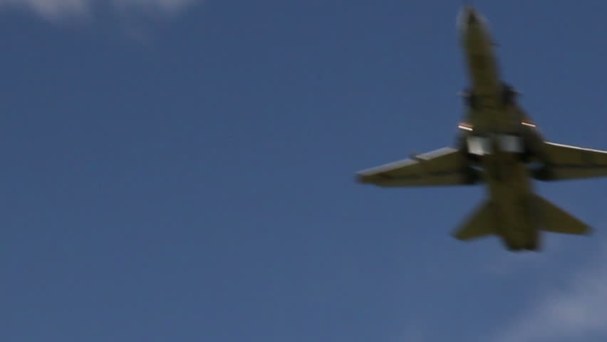 Military jet takes off in afterburner, against the sky.