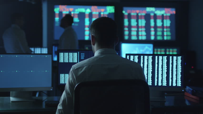 Stockbroker spotted a positive trend in trading charts while working in a dark monitoring room with display screens. Shot on RED Cinema Camera in 4K (UHD). | Shutterstock HD Video #14161628