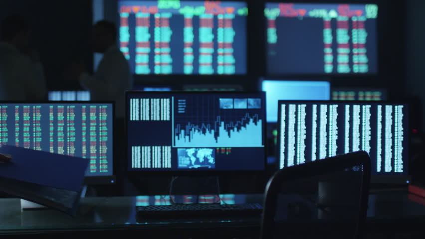 Stockbroker in white shirt is working in a dark monitoring room with display screens. Shot on RED Cinema Camera in 4K (UHD). | Shutterstock Video #14161637