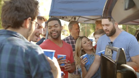 Slow Motion Shot Of Sports Fans Tailgating In Parking Lot
