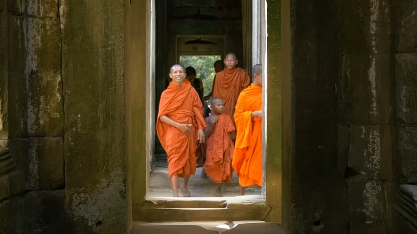 ANGKOR WAT, CAMBODIA - NOV 2015: Buddhist monk walking in temple. Slow motion orange robe buddhist monk walking in temple of Angkor Wat Cambodia ancient ruin of religious temple to meditate.