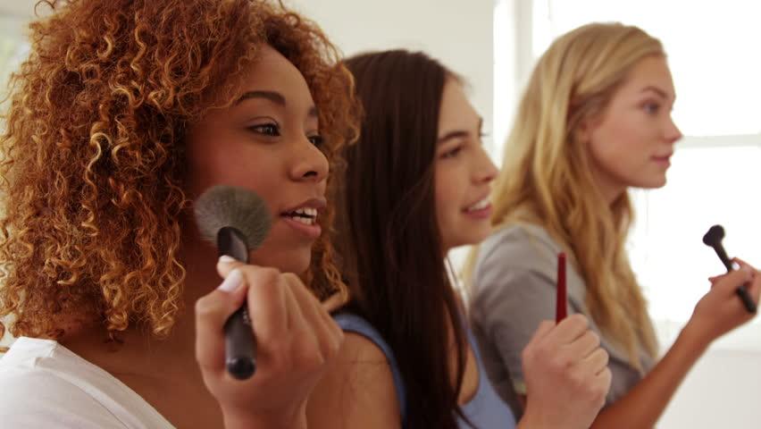 Smiling women applying make up between friend in the bathroom