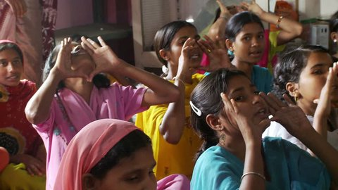 Baruipur, India - CIRCA 2013 - Girls in school sitting on mats singing and using hand gestures