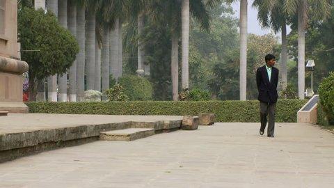 India - CIRCA 2013 - Man walking on the grounds of the Mulagandhakuti shrine at Sarnath.