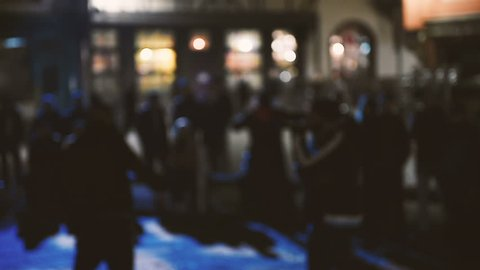 Panning over public street rap battle concert - defocused view of man singing in front of crowd and dancing under music
