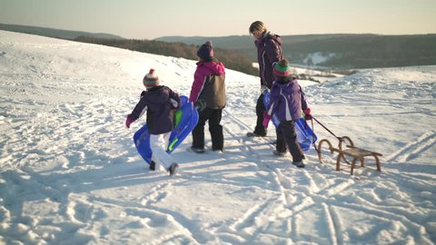 4k footage, mother with three young daughters walking outdoors in snow with bobsleds and sled up snowy hill