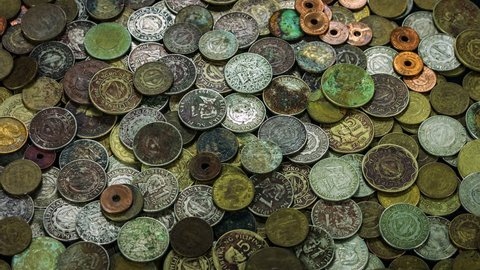 Old and ancient coins covered with copper and rust close up rotation.
