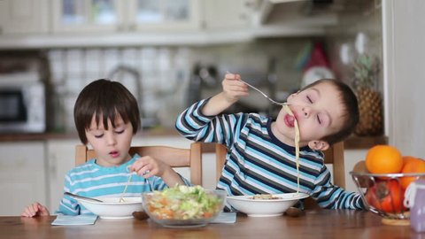 Two sweet children, boy brothers, having for lunch spaghetti at home, enjoying tasty food