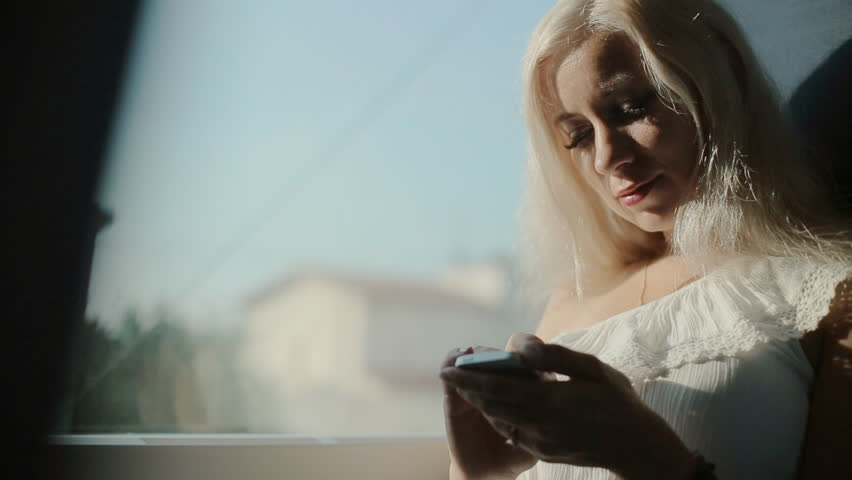 Attractive blonde writing sms on mobile phone  | Shutterstock HD Video #14252237