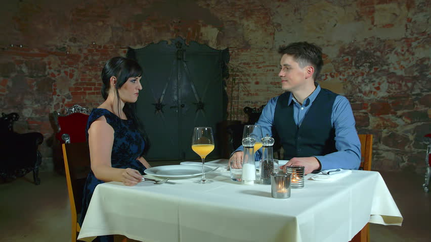 In this video, we can see a young couple enjoying a romantic dinner together. They make a toast and then they drink from their cups.