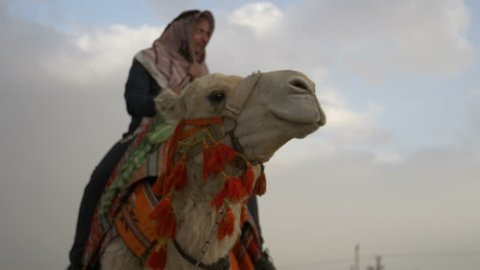 Arab male traditional headdress robe riding his camel over desert