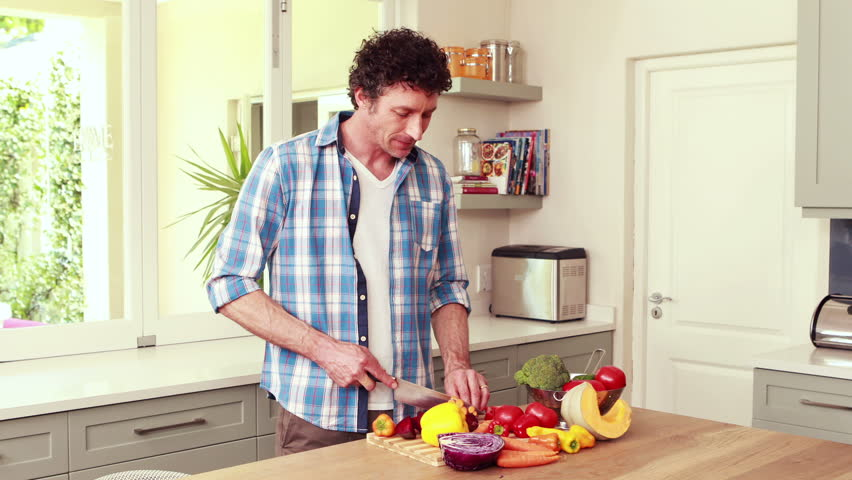 Woman Is Standing In The Kitchen Cutting Vegetables With Man ...