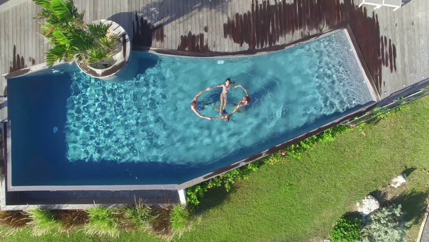 Aerial view of family in swimming pool making circle together | Shutterstock HD Video #14341357