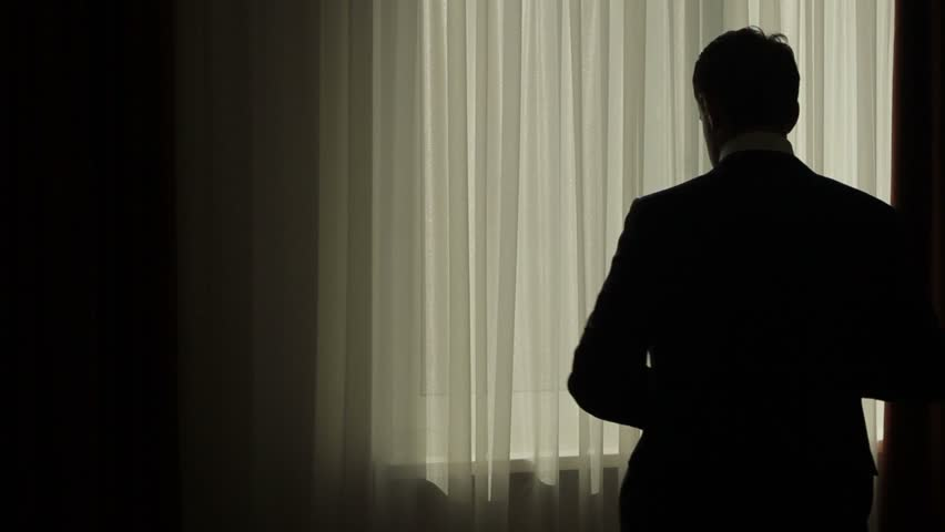 Business man puts on his jacket. Businessman dressed. Silhouette of a businessman on the background of the window. Handsome man preparing for a business meeting.   Shutterstock HD Video #14383927
