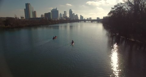 The camera starts low in a cove and then moves forward through the trees to reveal tourists and kayakers on Lady Bird Lake in Austin, Texas.  The camera progresses over the water and gains altitude.