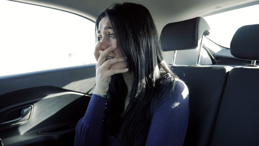 Sad woman crying in car back seat slow motion