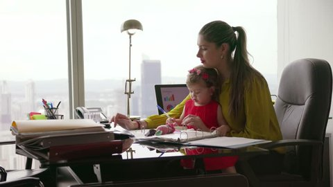 Adult businesswoman with her little baby in office. The multitasking mom plays with her child and writes document on tablet computer