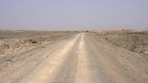 Slow Traffic on Desert Road. The car moves slowly through the desert, hot road. Bright sunshine