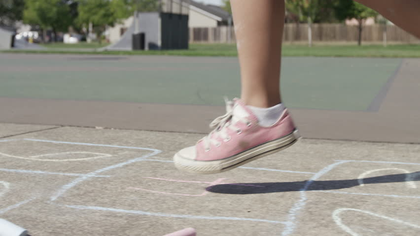 Young girl playing Hopscotch at park, closeup of feet