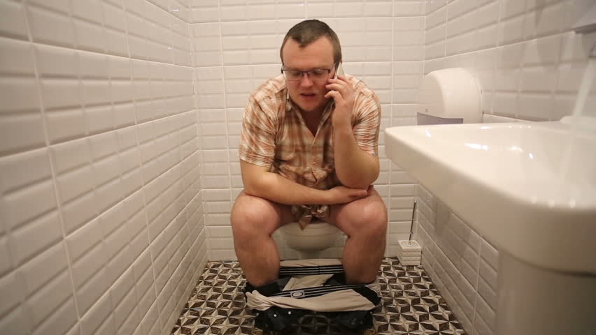 A man sits on a toilet and talking on the phone