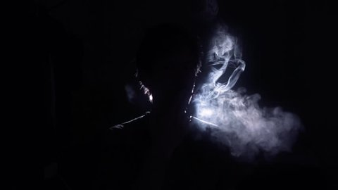 Cigarette smoker silhouette back lit man. Back Lit Silhouette of man smoking in a dark room - 1080p