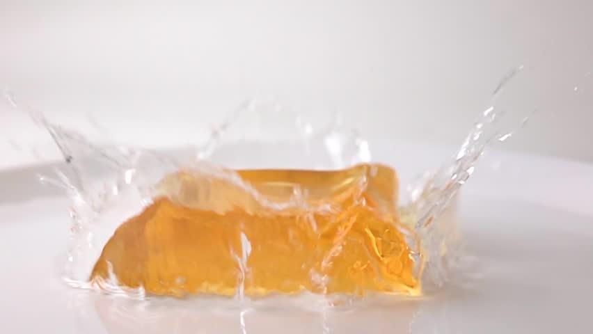 Macro super slow motion video of orange jelly falling in water