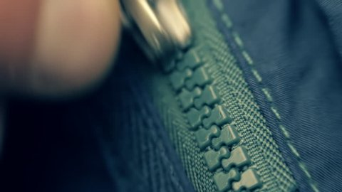 Hand unzipped and fasten blue plastic zipper on blue jacket. Extreme closeup. Shallow depth of field