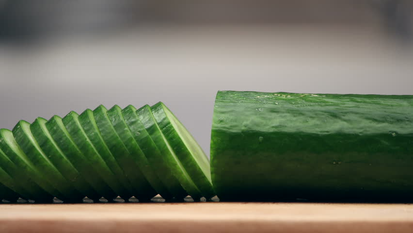 Slicing cucumber and lettuce. Closeup of chopped vegetables on wooden cutting board. Stop motion animation, 4K.