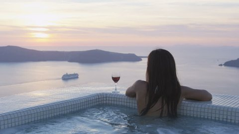 Luxury travel lifestyle woman in pool at sunset. Young woman having glass of red wine in swimming pool. Asian female is watching sunset over sea. She is enjoying her vacation on Santorini, Greece.
