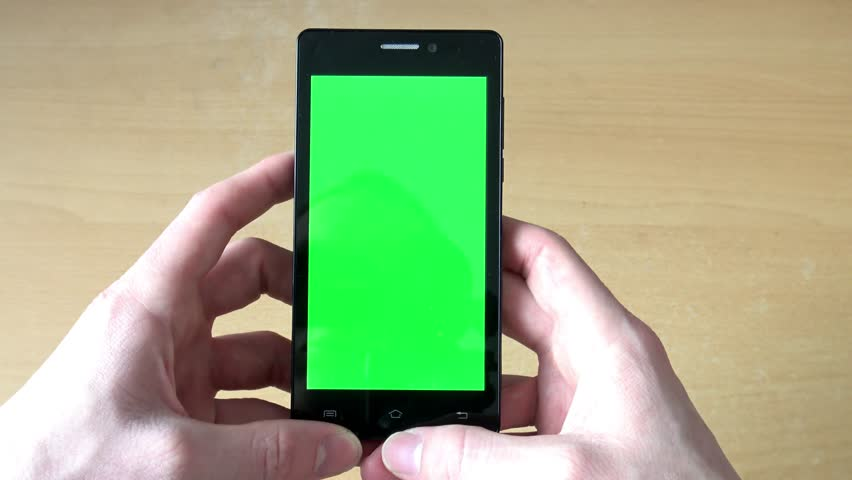 young man works (looks) on smartphone in office on the table - green screen - detail #14611447