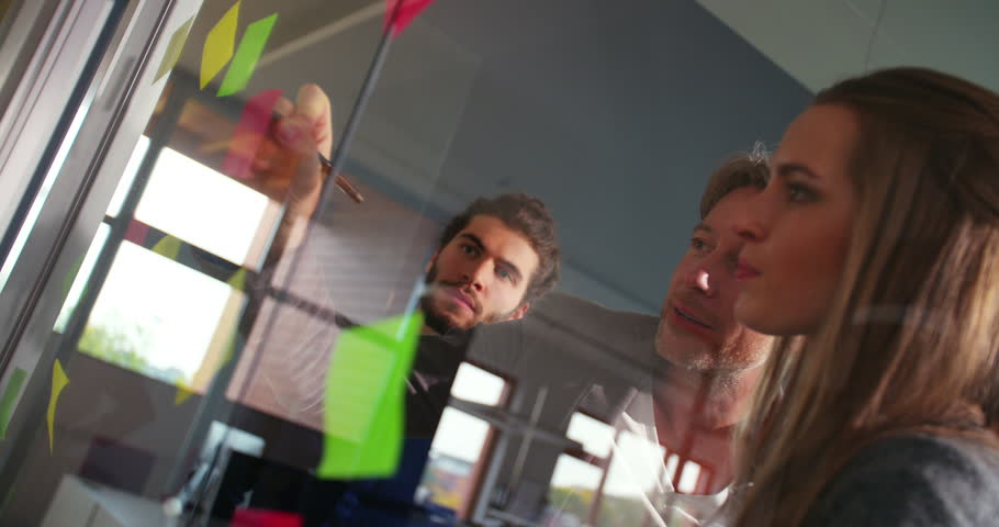 Young multi-ethnic start up team members listening attentively to executive business leaders brainstorming concept while they are creating a mind mapping board with post it notes on an office window