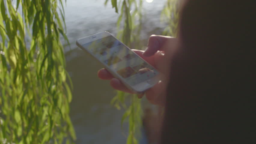 Closeup man using his smart phone by a river reflecting sunlight in slow motion #14699797