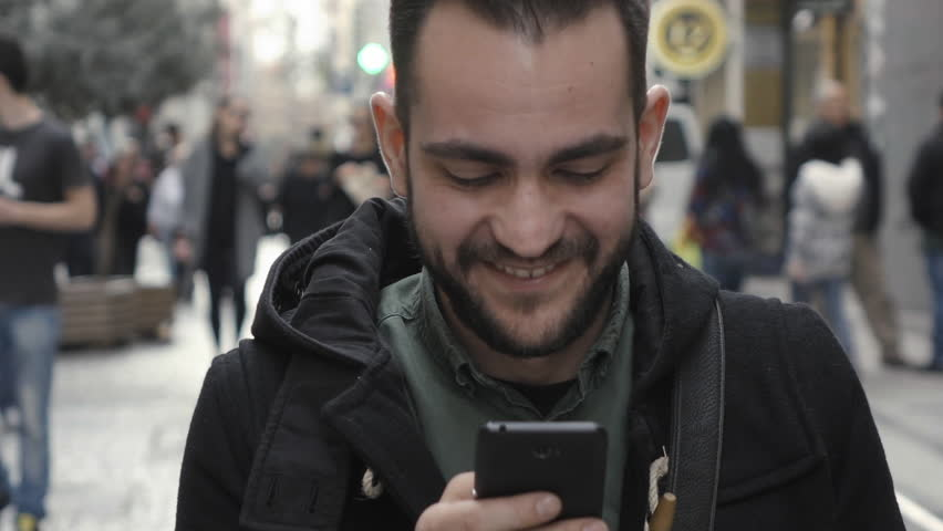 Young man using smartphone in public commercial street slomo.100p slow motion clip of a young man in casual war using a smartphone in the middle of a commercial street surrounded by shops and people | Shutterstock HD Video #14708218