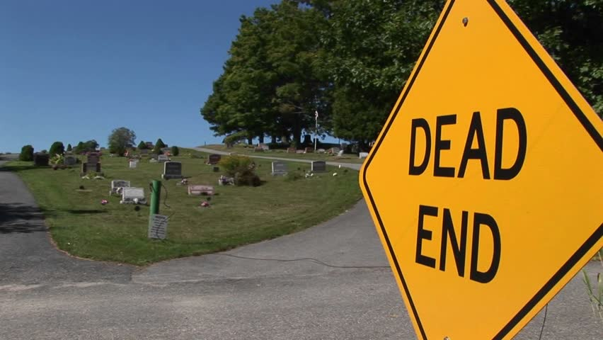 A dead end sign near a cemetery on a hillside.
